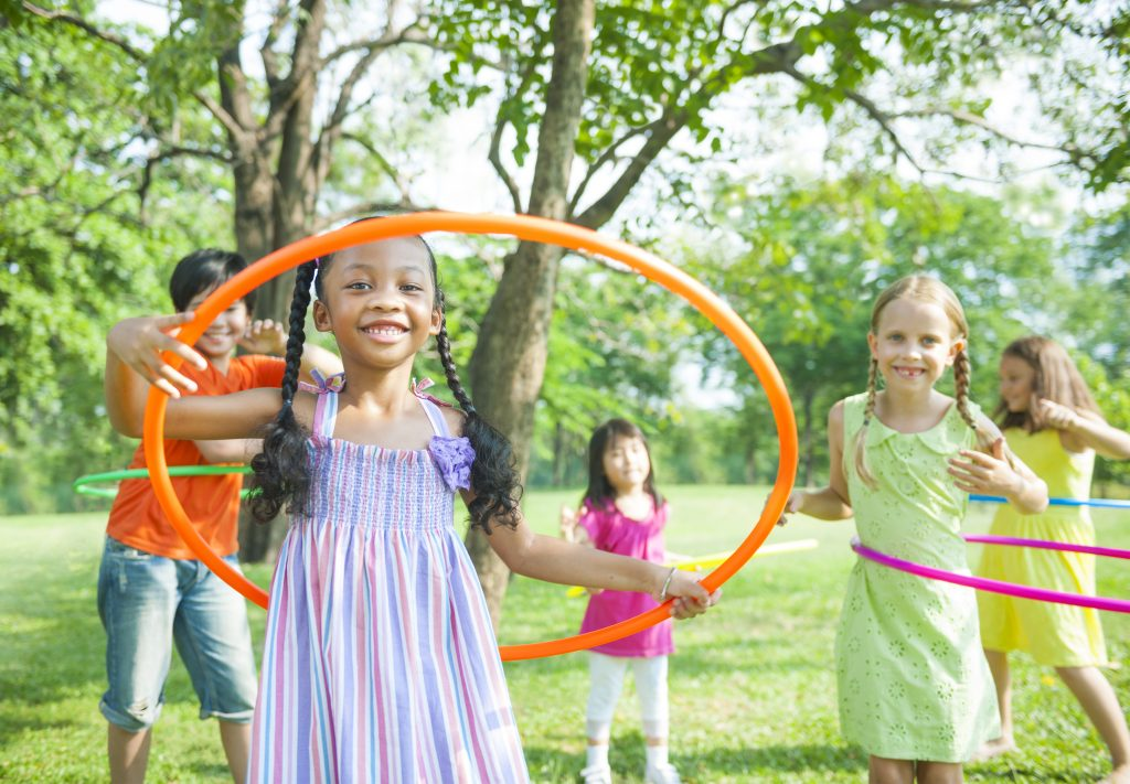 Group of children playing with hula hoops outside